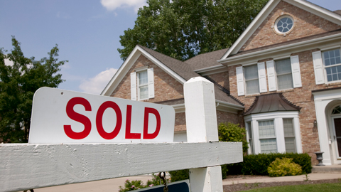 Image depicts a for sale sign in front of a house.