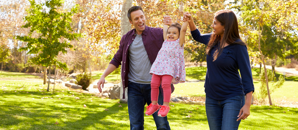 Image depicts a happy family outing in a park.